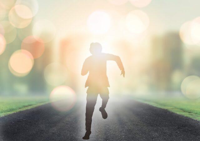 輝く未来へ走る男性シルエット